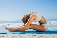 Gorgeous fit blonde in seated forward bend pose on the beach Stock Photo