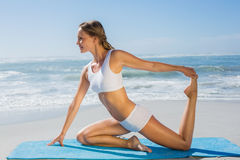 Gorgeous fit blonde in seated yoga pose on the beach Royalty Free Stock Image