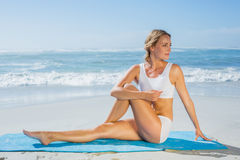 Gorgeous fit blonde in seated yoga pose on the beach Royalty Free Stock Photography