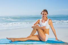 Gorgeous fit blonde in seated yoga pose on the beach Stock Photo