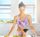 Gorgeous fit woman making fresh fruit juice Royalty Free Stock Photo