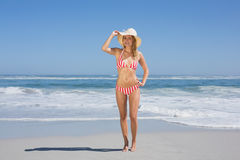 Gorgeous fit woman in striped bikini and sunhat at beach Royalty Free Stock Photo