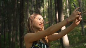 Gorgeous fitness girl taking selfie with smartphone in the forest. Beautiful fitness girl using mobile phone outdoors stock video