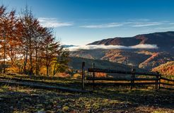 Gorgeous foggy morning in mountainous countryside. Beautiful landscape with wooden fence and trees with yellow foliage on hillsides in late autumn Royalty Free Stock Photos