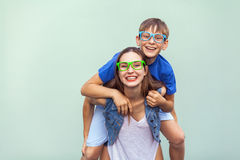 The gorgeous freckled brother and sister in casual t shirts wearing trendy glasses and posing over light blue background together Stock Image