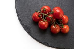 Gorgeous fresh cherry tomatoes. Great quality close up photo of fresh ripe cherry tomatoes on green branch served on a stylish natural black shale surface. Some Royalty Free Stock Photography