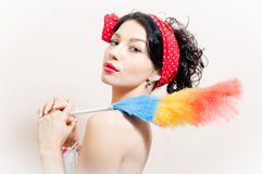 Gorgeous funny pinup woman removing dust. Gorgeous pretty funny young black-haired pinup woman removing dust royalty free stock image