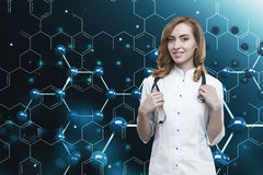 Gorgeous ginger doctor and a blue atom grid Royalty Free Stock Photo