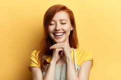 Gorgeous ginger girl with closed eyes laughing at somebody royalty free stock photos
