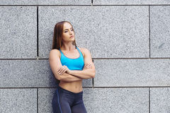 Gorgeous ginger sport figure fitness female posing with muscles in sportswear outdoors. Grey wall in background. Stock Photos