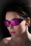 Gorgeous girl. Beautiful brunette with funky sunglasses on black background Royalty Free Stock Images