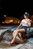 Gorgeous girl with american flag and heels. Beautiful girl wearing short pants and red heels in town at night Royalty Free Stock Image