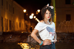 Gorgeous girl with american flag on t -shirt. Gorgeous curly girl wearing american flag on tshirt sitting next to fountain at night Royalty Free Stock Images