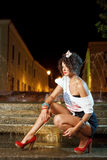 Gorgeous girl with american flag on t -shirt. Gorgeous curly girl wearing american flag on tshirt sitting next to fountain at night Royalty Free Stock Photo