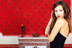 Gorgeous girl in black dress posing in a vintage room on a red b Royalty Free Stock Photo