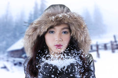 Gorgeous girl blowing snow on her palms Royalty Free Stock Image