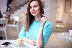 Gorgeous girl with curly hairstyle waiting friend in restaurant with cozy interior and drink cofe. Good-looking young woman lookin. Gorgeous girl with curly Stock Photo