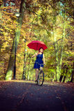Gorgeous girl cycling with umbrella. Stock Photography