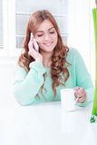 Gorgeous girl drinking coffee and talking on the phone Royalty Free Stock Photos