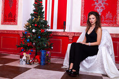 Gorgeous girl in evening dress in red vintage room with christma Stock Photo