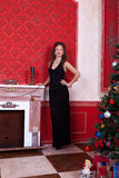 Gorgeous girl in evening dress in red vintage room with christma Royalty Free Stock Photo