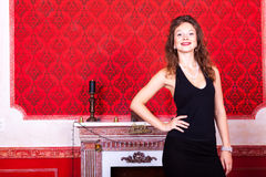 Gorgeous girl in evening dress in red vintage room with christma Royalty Free Stock Images