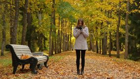 Gorgeous girl feels cold and stands near some bench in autumn park. Beautiful girl stands near a wooden bench in a picturesque autumn park, dressed in grey coat stock video footage