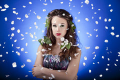 Gorgeous girl with flowers in hair and with flying petals around Stock Image