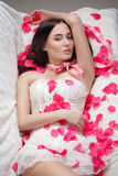 Gorgeous girl lying in rose petals. Stock Image