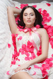 Gorgeous girl lying in rose petals. Royalty Free Stock Photography