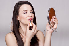 Gorgeous girl with mirror. Pretty woman holding a mirror with lipstick Stock Photos