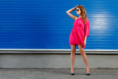 Gorgeous girl in pink dress. Next to blue industrial wall wearing heels and glasses Royalty Free Stock Photography