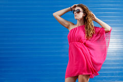 Gorgeous girl in pink dress. Next to blue industrial wall wearing heels and glasses Stock Images
