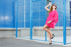 Gorgeous girl in pink dress. Next to blue industrial wall wearing heels and glasses Royalty Free Stock Image