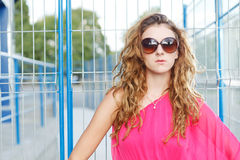 Gorgeous girl in pink dress. Next to blue industrial wall wearing glasses Stock Photo