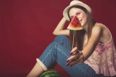 Gorgeous girl with pink make up, wearing jeans, hat and top, posing at red studio background, holding slice watermelon on stick,. Looking at camera and smile royalty free stock photography