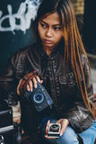 Gorgeous girl posing holding light meter and photo camera, hipster style Royalty Free Stock Image