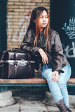 Gorgeous girl posing with leather bag, hipster style. Girl posing in leather jacket and leather bag beside her Royalty Free Stock Photography
