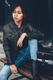 Gorgeous girl posing with leather bag, hipster style. Girl posing sitting on the bench with leather bag Stock Photos