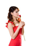 Gorgeous girl with a red rose. Beautiful young woman in a red dress holding a rose bud for her valentine Royalty Free Stock Photo