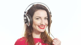 Gorgeous girl in red swaying along with the music in big headphones noticing camera and shying isolated on white background close stock video