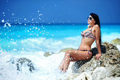 Gorgeous girl relaxing on a tropical beach. A shot taken in Greece of a young sexy brunette girl on a tropical beach in Lefkada island Royalty Free Stock Images