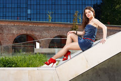 Gorgeous girl sitting. Handsome girl wearing short skirt and red heels sitting down outside in urban landscape in a sunny day Stock Image
