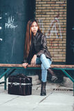 Gorgeous girl sitting on the bench outside with leather bag, hipster style Royalty Free Stock Images