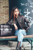 Gorgeous girl sitting on the bench outside with leather bag, hipster style Stock Image
