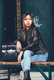 Gorgeous girl sitting on the bench outside with leather bag, hipster style Stock Photos
