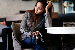 Gorgeous girl sitting on a nice chair with photo camera in her hands. Beautiful girl sitting on a chair holding camera Royalty Free Stock Photos