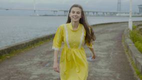 Gorgeous girl stands on a pier and smiles with a bridge in the background in slo-mo stock video