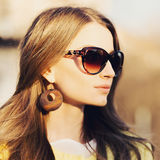 Gorgeous girl in sunglasses and big rounded wooden earrings. Royalty Free Stock Photography