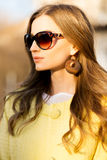 Gorgeous girl in sunglasses and big rounded wooden earrings. Royalty Free Stock Photo